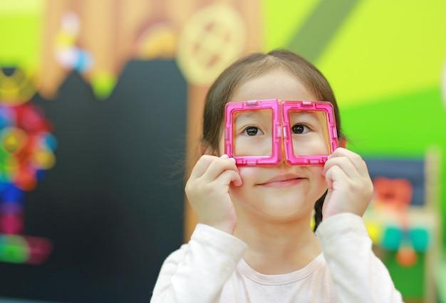 Das kleine kindermädchen, das magneten spielt, spielen für gehirnentwicklung.
