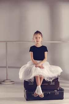 Das kleine mädchen als balerina-tänzerin sitzt im studio