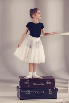 Das kleine mädchen als balerina-tänzerin steht im studio