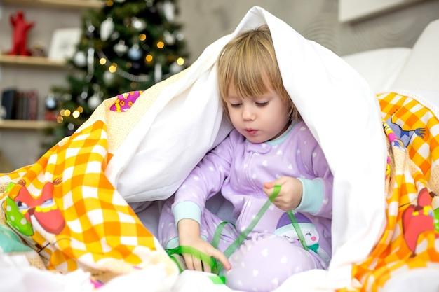 Das kleine mädchen am weihnachtsmorgen versteckt sich unter der decke im zimmer mit dem weihnachtsbaum