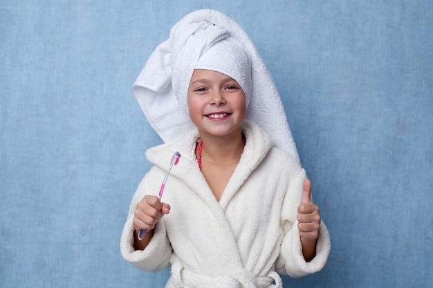 Das kleine mädchen, das eine zahnbürste in ihrer hand hält und daumen zeigt, up geste