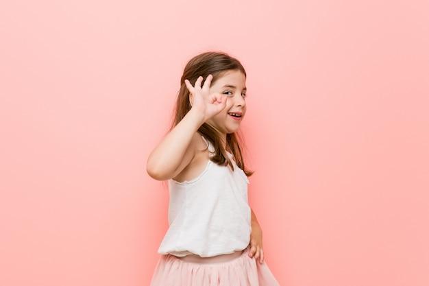 Das kleine mädchen, das einen prinzessinblick trägt, blinzelt ein auge und hält eine okaygeste mit der hand.