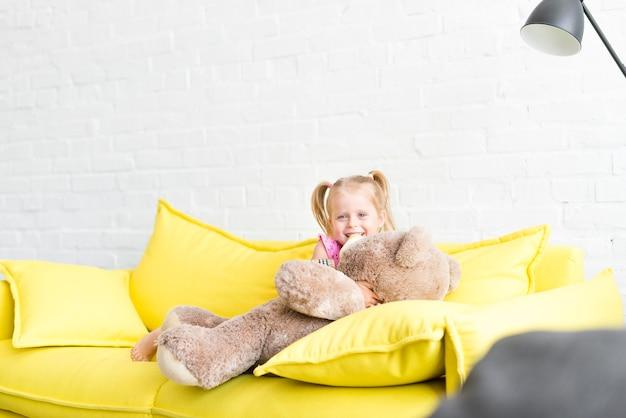 Das kleine mädchen, das mit ihrem teddy spielt, betreffen das sofa