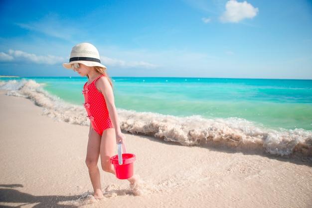 Das kleine mädchen, das mit strand spielt, spielt während der tropischen ferien