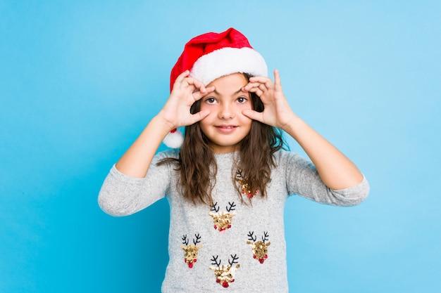 Das kleine mädchen, das weihnachtstag augen halten feiert, öffnete sich, um eine erfolgschance zu finden.
