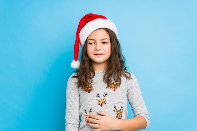 Das kleine mädchen, das weihnachtstag feiert, berührt bauch, lächelt leicht und isst und zufriedenheitskonzept.