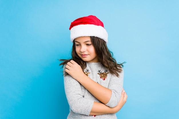 Das kleine mädchen, das weihnachtstag feiert, umarmt und lächelt sorglos und glücklich.