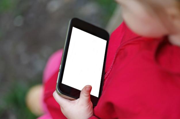 Das kleine mädchen hält smartphone. bildschirm mit leeren weißen textfreiraum.