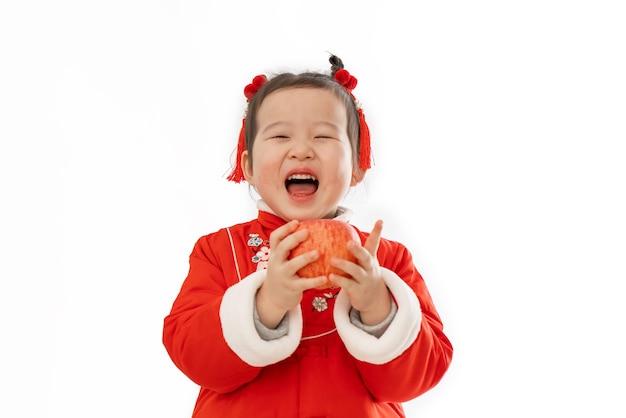 Das kleine mädchen in traditioneller chinesischer kleidung hat einen apfel in der hand