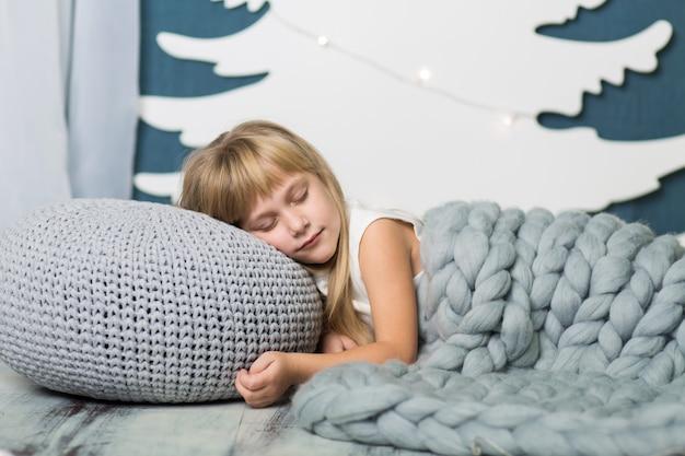 Das kleine mädchen liegt schlafend auf einem kissen, das mit einer grauen strickdecke bedeckt ist