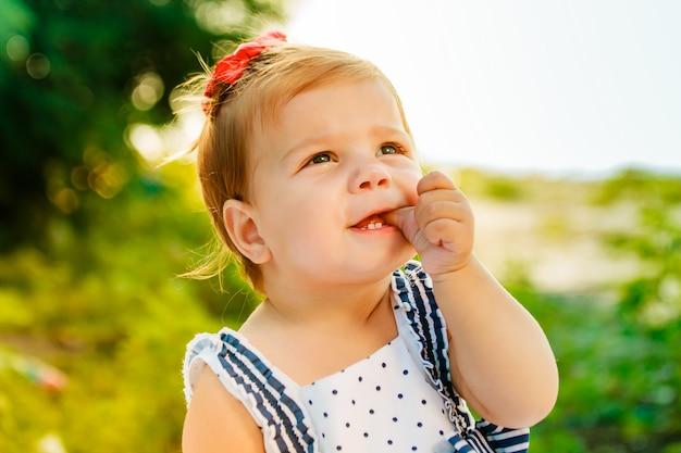 Das kleine mädchen mit dem kurzen haar saugt finger. das baby schaut in den himmel. kleines schönes kind, das auf der bank des flusses unter den grünen bäumen sitzt.