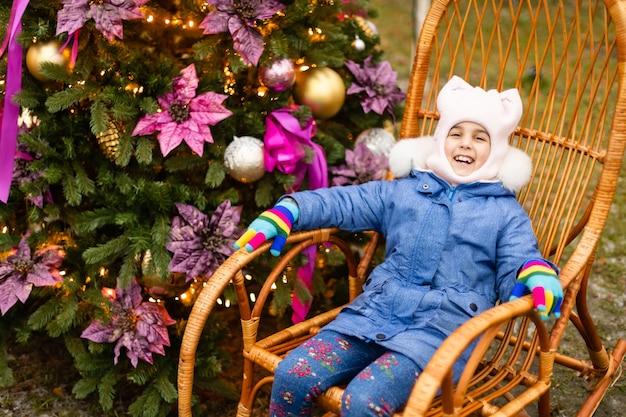 Das kleine mädchen neben dem geschmückten weihnachtsbaum mit geschenken