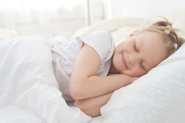 Das kleine mädchen schläft morgens gerne und wacht nicht auf. früher morgen