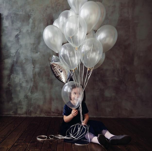 Das kleine mädchen sitzt auf dem boden und hält ballons im raum