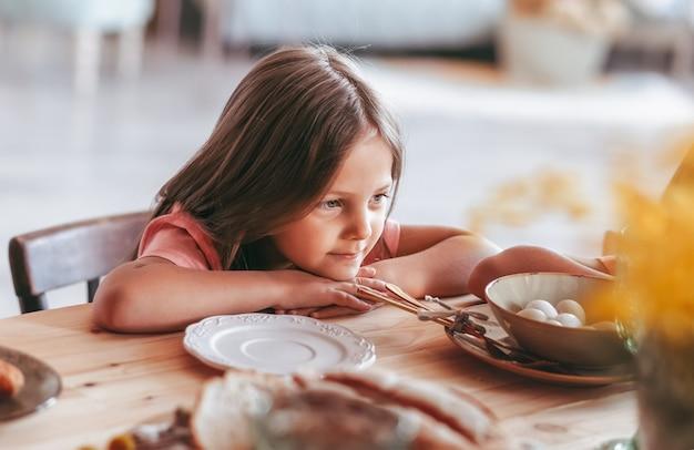 Das kleine mädchen sitzt mit einem nachdenklichen blick auf den küchentisch.