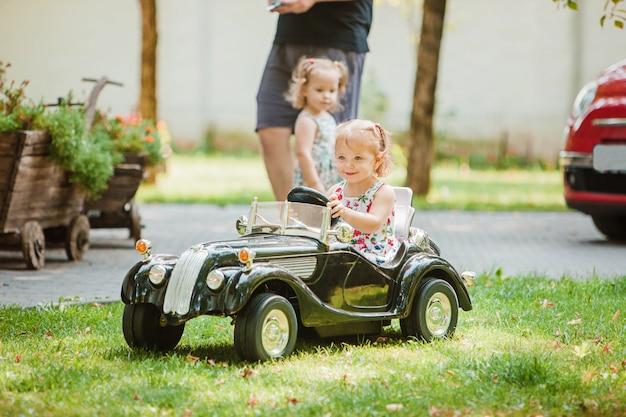 Das kleine mädchen spielt am auto