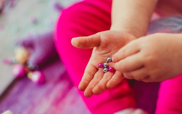 Das kleine mädchen spielt mit bällen und steinen