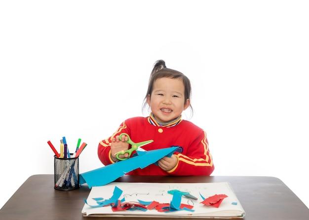 Das kleine mädchen spielt mit dem papierschneiden