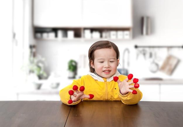 Das kleine mädchen spielte mit himbeeren an den fingern