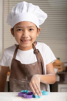 Das kleine mädchen trug eine weiße kochmütze und eine braune schürze, die kekse machte