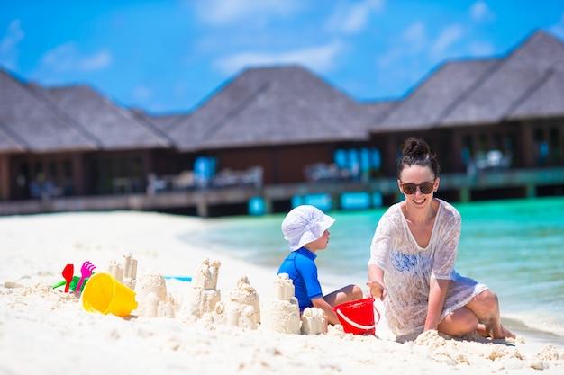 Das kleine mädchen und glückliche mutter, die mit strand spielen, spielt auf sommerferien