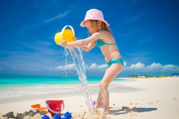 Das kleine nette mädchen, das mit strand spielt, spielt während der tropischen ferien