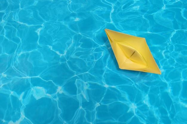 Das kleine papierschiff auf dem wasserhintergrund. minimales konzept sommer und reise flach liegen
