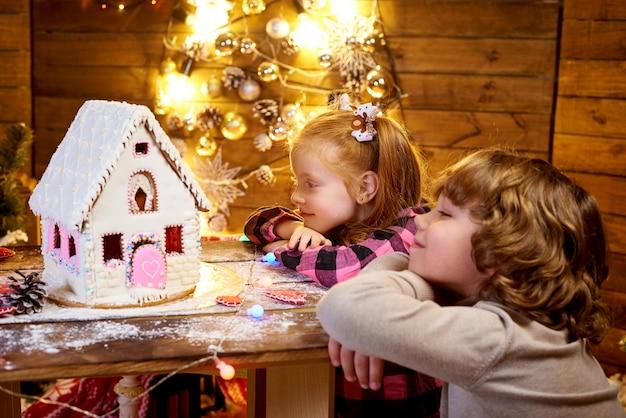 Das kleine rothaarige mädchen schaut mit interesse auf den weihnachtslebkuchen.