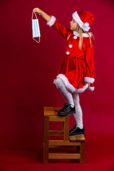 Das kleine weihnachtsmädchen steigt auf eine leiter und möchte etwas mit einer maske verzieren, die auf rot isoliert ist