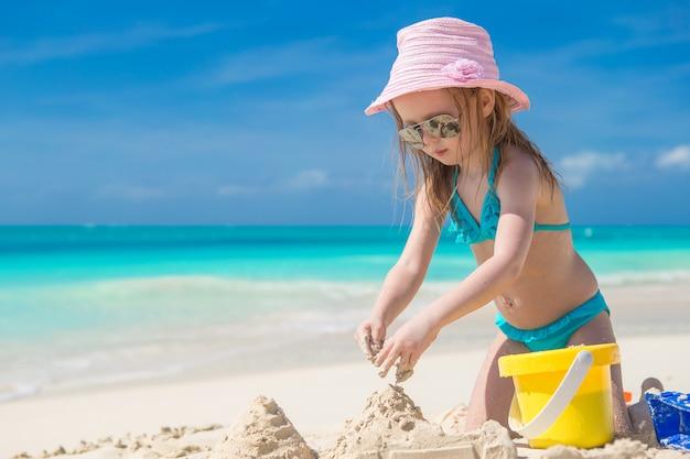 Das kleinkind, das mit strand spielt, spielt während der tropischen ferien