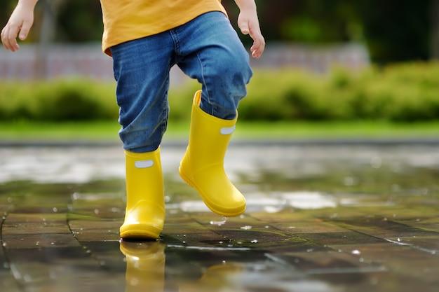 Das kleinkind springend in wasserbecken am sommer- oder herbsttag