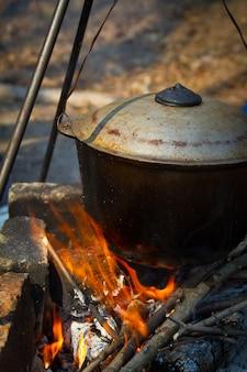 Das konzept der campingküche, auf einem stativ über dem feuer steht ein topf, in dem essen zubereitet wird