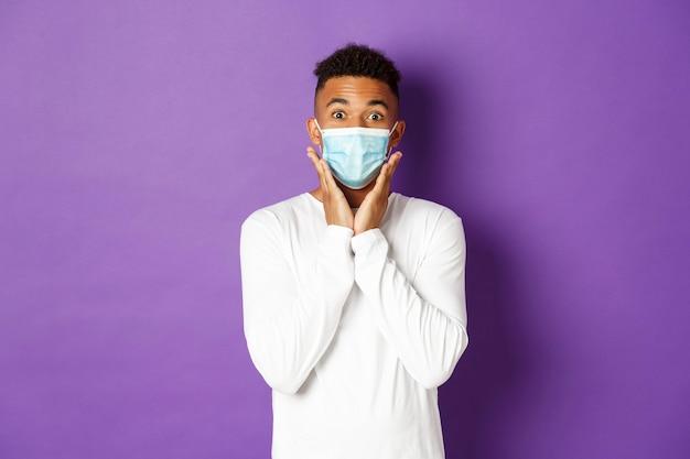 Das konzept der covid-pandemie und der sozialen distanzierung überraschte den afroamerikanischen mann mit medizinischer maske und...