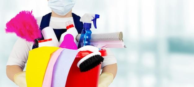Das konzept der desinfektion und reinigung in innenräumen. eine putzfrau in gummihandschuhen hält einen eimer voller chemikalien