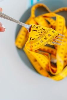 Das konzept der diät. der gabel zurückgespulte zentimeter, der auf plattennahaufnahme liegt
