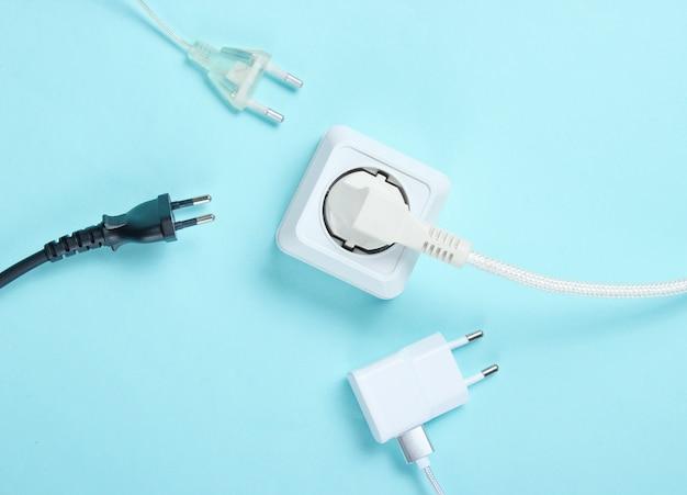 Das konzept der elektrischen abhängigkeit. viele netzstecker in der nähe von steckdosen