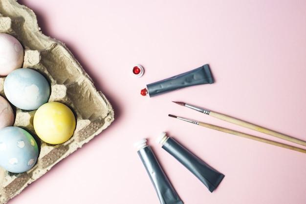 Das konzept der färbung von ostereiern in pastellaquarellfarben. farben und pinsel zum färben von eiern für ostern auf rosa hintergrund
