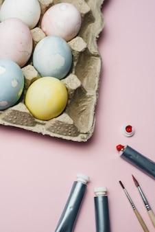 Das konzept der färbung von ostereiern in pastellaquarellfarben. farben und pinsel zum färben von eiern zu ostern auf rosa oberfläche