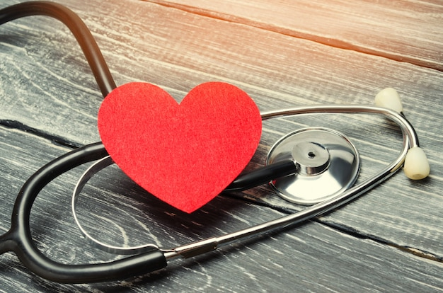 Das konzept der familienmedizin und versicherung. stethoskop und herz auf einem hölzernen hintergrund