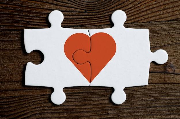 Das konzept der gegenseitigen liebe. stücke eines verbundenen weißen puzzlespiels mit rotem herzen auf einem hölzernen hintergrund.