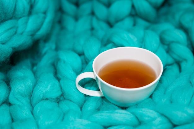 Das konzept der gemütlichkeit und des komforts ist eine grüne strickdecke, auf der eine weiße tasse tee steht. nahaufnahme.