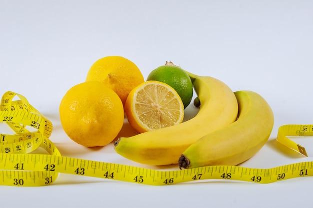 Das konzept der gesunden ernährung, gewichtsverlust ,. bananen, zitrone, maßband auf dem tisch.