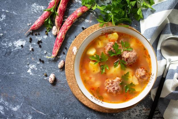 Das konzept der gesunden und diätetischen nahrung gemüseherbstsuppe mit bohnenbällchen auf einem tisch draufsicht