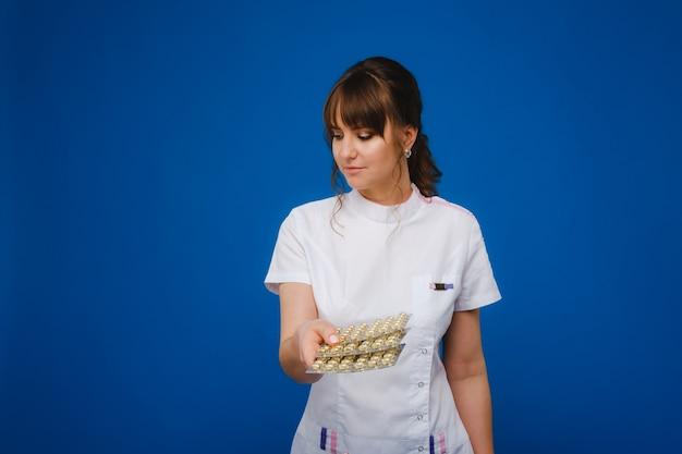 Das konzept der gesundheitsversorgung. eine junge brünette ärztin in einem weißen kittel auf blauem grund zeigt teller mit kapseln zum einnehmen.
