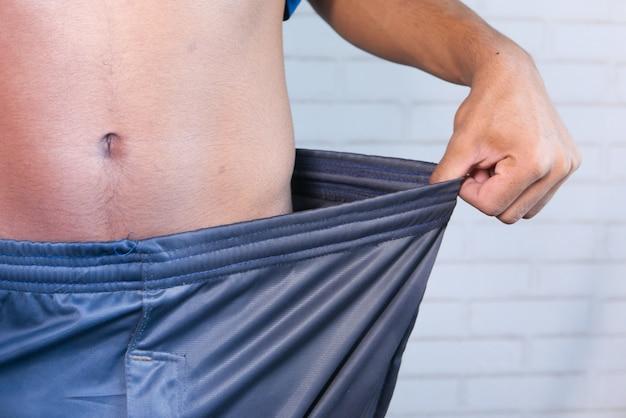 Das konzept der gewichtsabnahme, junger mann zieht hose