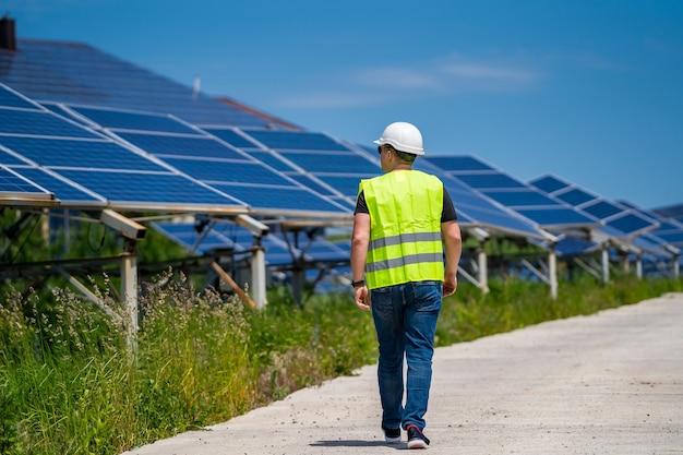 Das konzept der grünen neuen energie. ingenieur bei solaranlage. zu fuß zu den sonnenkollektoren.