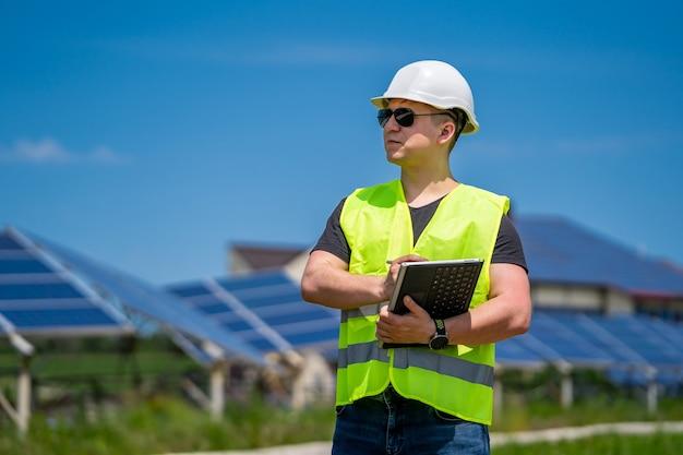 Das konzept der grünen neuen energie. solarbasistechniker besprechen erneut planung und wartung.