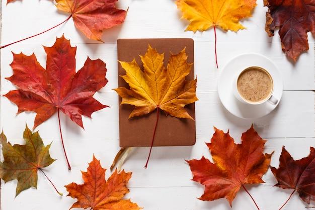 Das konzept der herbststimmung. morgenkaffee, tagebuch und farbige ahornblätter.