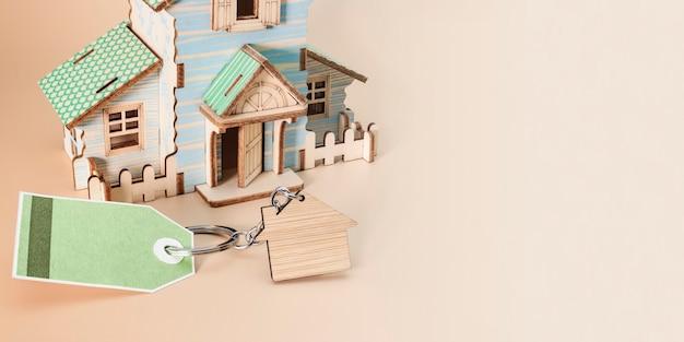 Das konzept der hypothek, des verkaufs und der vermietung von wohnungen und immobilien. ein haus kaufen. ein modell des hauses auf einem zarten beigen hintergrund. tag mit platz für text. bannerformat. platz kopieren.