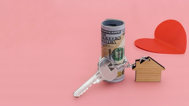 Das konzept der hypothek, des verkaufs und der vermietung von wohnungen und immobilien. hypothekendarlehen. hausförmiger schlüsselanhänger mit schlüsseln und dollarnoten auf rosa hintergrund. platz kopieren.